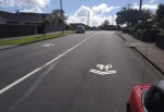 Properly located sharrows will steer bikes out past parked cars (c/ Akld Transport)
